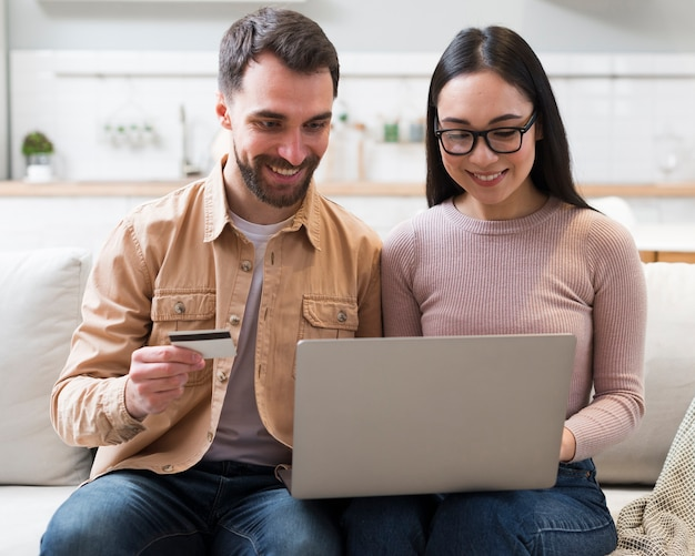 Front view of smiley couple shopping online