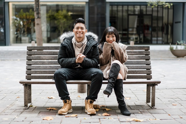 Front view of smiley couple sitting on a bench