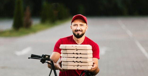 Front view smiley delivery guy holding pizza boxes