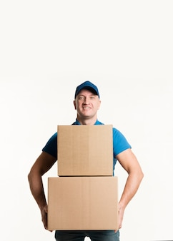 Front view of smiley delivery man holding cardboard boxes