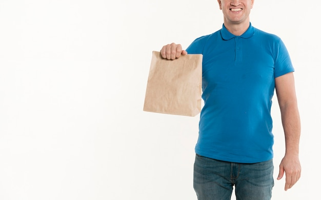 Front view of smiley delivery man holding paper bag