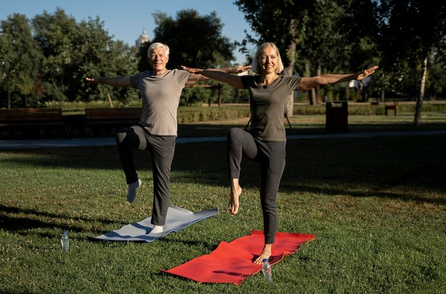 Front view of smiley elder couple practicing yoga outdoors