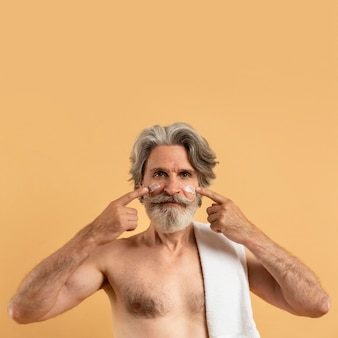 Front view of smiley elder man with beard applying cream on face with copy space