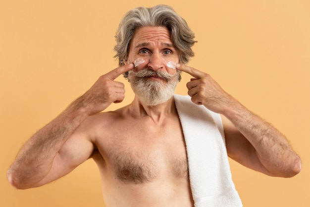 Front view of smiley elder man with beard applying cream on face