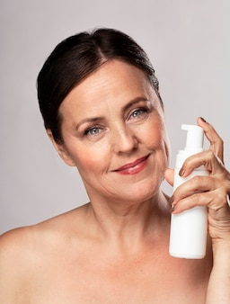 Front view of smiley elder woman holding bottle of cleanser for skincare