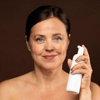Vista frontale della donna anziana di smiley che tiene una bottiglia di detergente