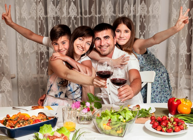 Front view of smiley family at dinner table