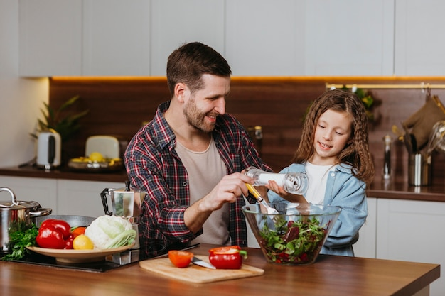 Front view of smiley father with daughter preparing food in the kitchen