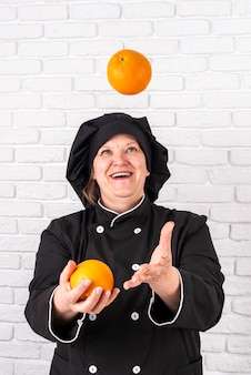 Front view of smiley female chef joggling with oranges