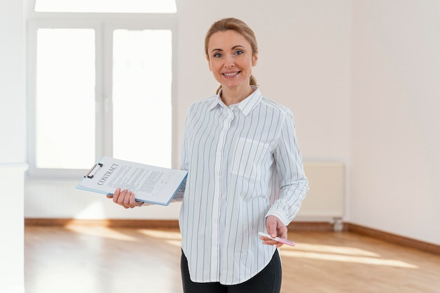 Front view of smiley female realtor in empty house holding clipboard