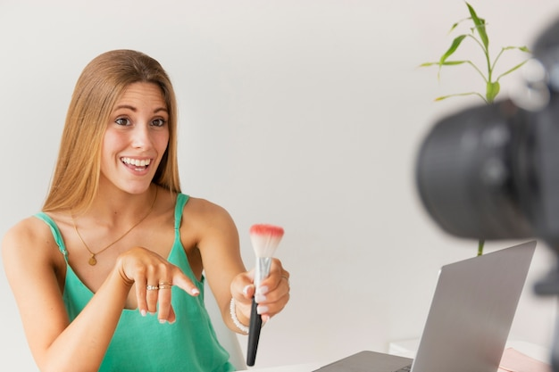 Front view smiley female showing makeup brush to camera