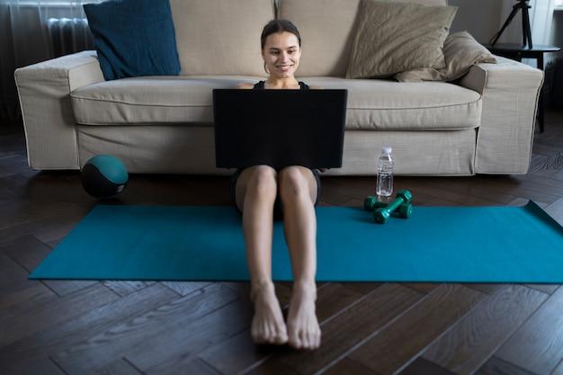 Vista frontale della femmina di smiley con il computer portatile