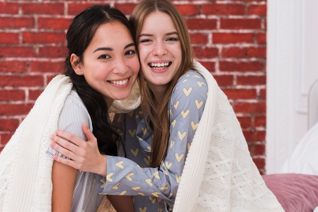 Front view smiley females sharing blanket