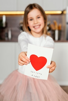 Front view of smiley girl holding a card for father's day