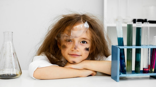 Front view of smiley girl scientist in the laboratory with test tubes and failed experiment
