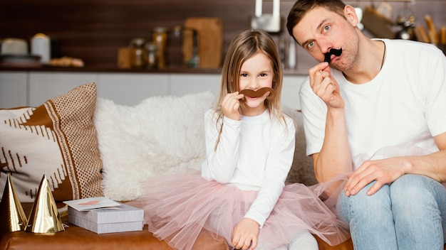 Front view of smiley girl in tutu skirt and father with fake mustaches