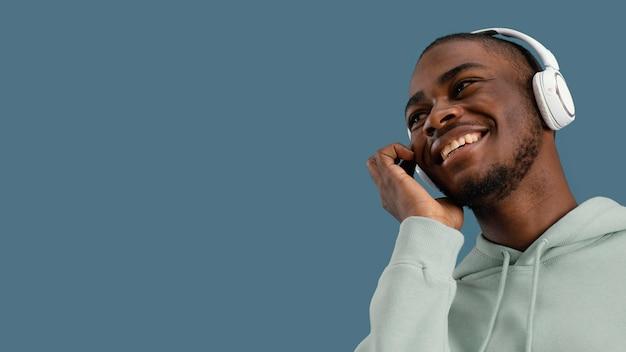 Vista frontale dell'uomo bello di smiley con le cuffie e lo spazio della copia