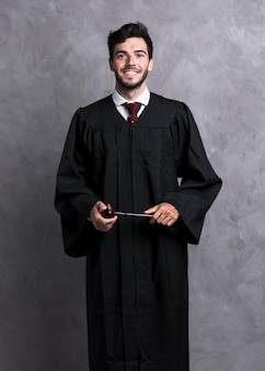 Front view smiley judge in robe holding wooden gavel
