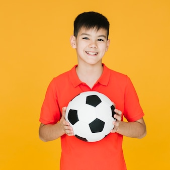 Front view smiley kid holding a football ball