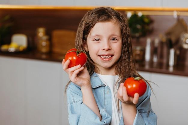 Vista frontale della bambina sorridente in cucina con i pomodori