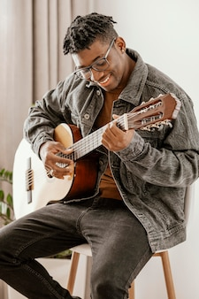 Front view of smiley male musician playing guitar at home