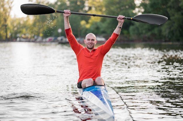 Front view smiley man in canoe with oar
