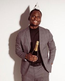 Front view smiley man holding a bottle of champagne