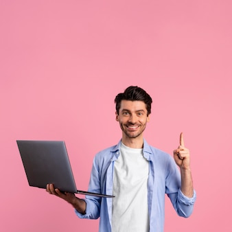 Front view of smiley man holding laptop and pointing up