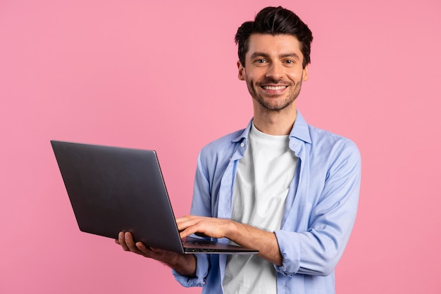 Front view of smiley man holding laptop
