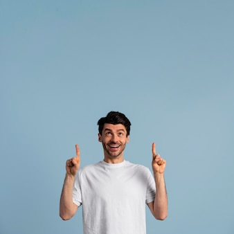 Front view of smiley man looking and pointing up