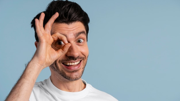 Front view of smiley man making ok sign with hand covering his eye
