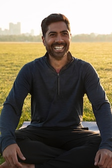 Vista frontale dell'uomo sorridente che medita all'aperto sul tappetino da yoga