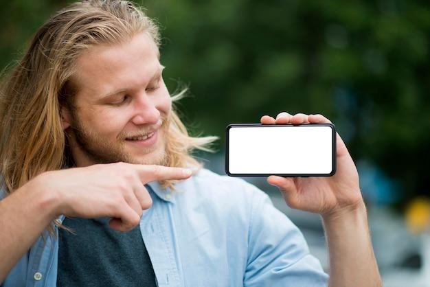 Vista frontale dell'uomo di smiley che indica al telefono