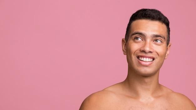 Vista frontale dell'uomo di smiley che posa senza camicia con lo spazio della copia
