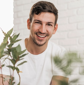 Front view of smiley man sitting next to plants