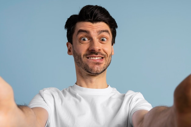 Front view of smiley man taking a selfie