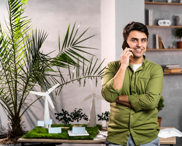 Vista frontale dell'uomo sorridente che parla al telefono accanto a un layout di progetto di energia eolica ecologico