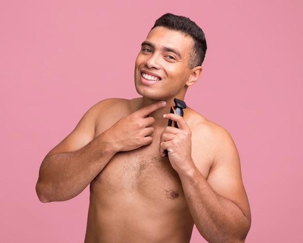 Vista frontale dell'uomo sorridente utilizzando un rasoio elettrico