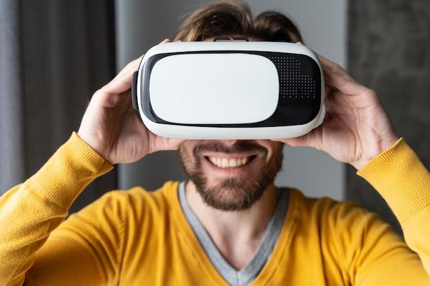 Vista frontale dell'uomo sorridente utilizzando le cuffie da realtà virtuale