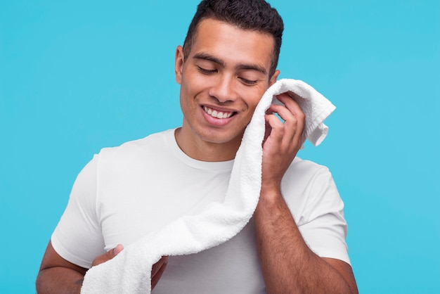 Front view of smiley man wiping his face with clean towel