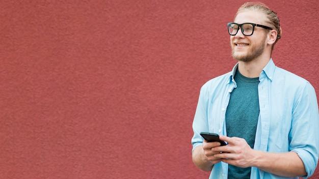 Vista frontale dell'uomo di smiley con lo spazio e lo smartphone della copia