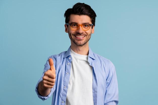 Vista frontale dell'uomo sorridente con gli occhiali che mostra i pollici in su