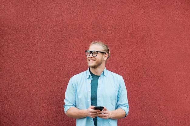 Vista frontale dell'uomo di smiley con lo smartphone