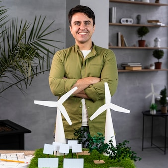 Vista frontale dell'uomo sorridente che lavora a un progetto di energia eolica ecologico con turbine eoliche