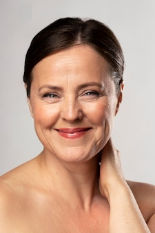 Front view of smiley mature woman posing with make-up on