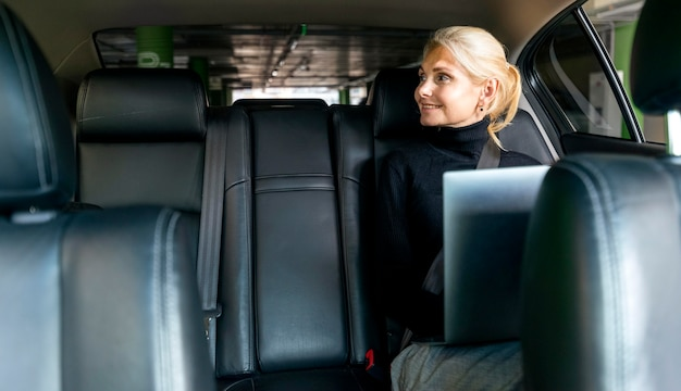 Front view of smiley older business woman working on laptop in car