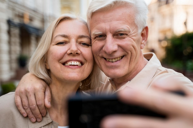 Front view of smiley senior couple taking a selfie while out in the city