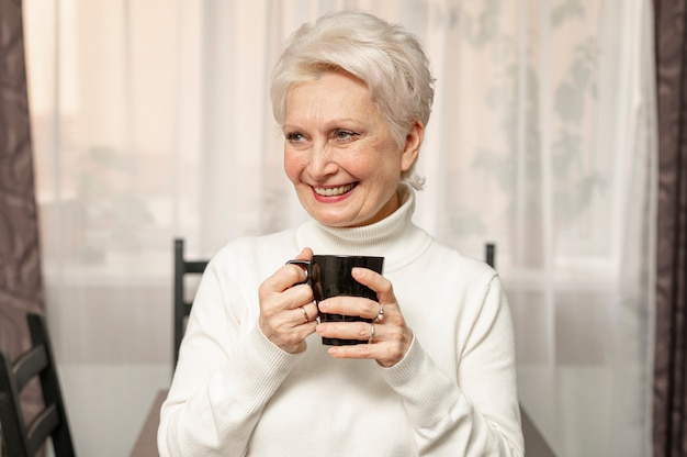 Front view smiley senior female holding cup of coffee