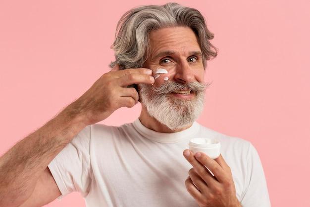 Vista frontale dell'uomo senior di smiley con la barba che applica crema