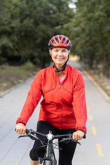 Vista frontale della donna senior di smiley all'aperto equitazione bicicletta